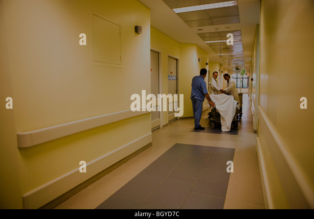 Healthcare workers treating patient on gurney in hospital corridor - Stock Image