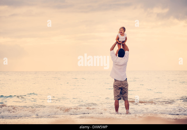 Father and Daughter Playing Together at the Beach at Sunset. Happy Fun Smiling Lifestyle - Stock Image