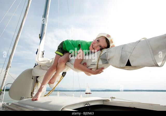 young girl lying on mast of sailing ship - Stock Image