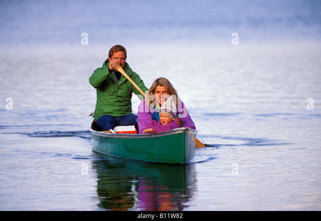A family canoes across a placid lake and scrutinize the shore for signs of wildlife - Stock Image