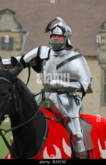 Red knight in armour on horseback - Stock Image