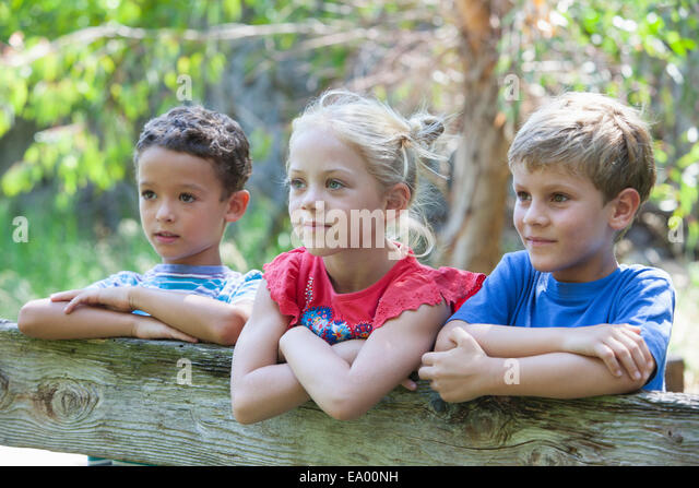 Three children leaning on fence looking away - Stock Image