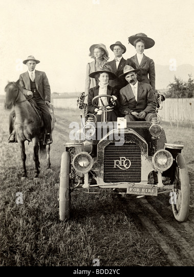 Five People in Antique Reo Auto & Man on Horseback - Stock Image