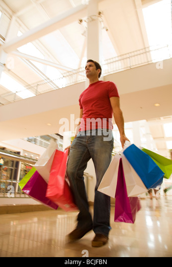 Caucasian male walking in shopping center mall holding shopping bags of various colors. - Stock Image