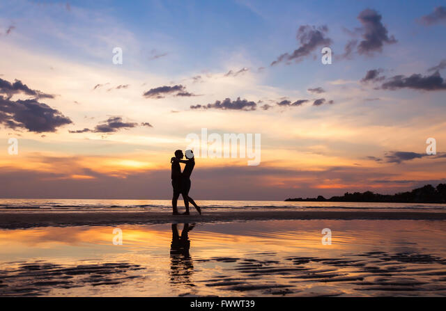 silhouette of couple on sunset beach, beautiful background about love and relationships, man and woman - Stock Image