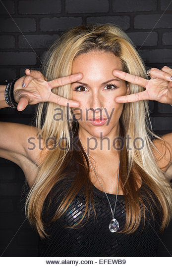 Portrait of cool blonde woman gesturing peace sign - Stock-Bilder