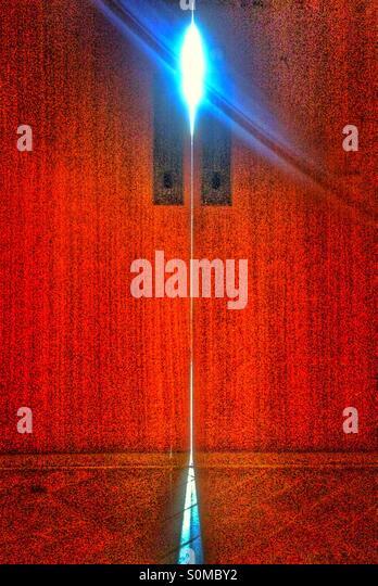 Red door with light peeking through - Stock Image