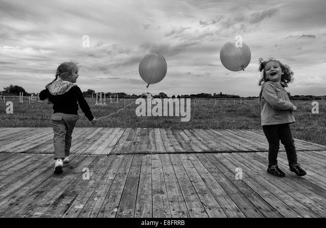 Two girls (4-5) playing with balloons - Stock Image