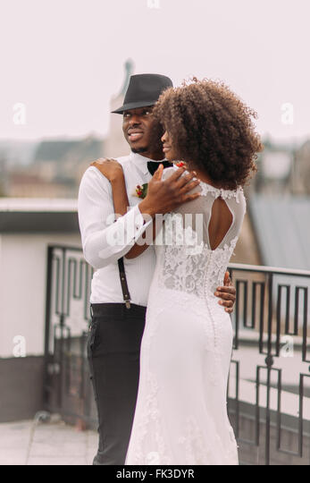 Beautiful black newlyweds softly hugging on the rooftop - Stock Image