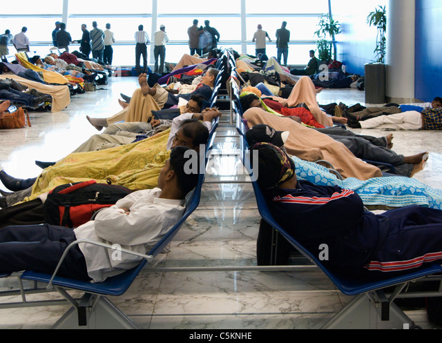 Men asleep in departure lounge area, some covered in blankets, Dubai Airport - Stock Image