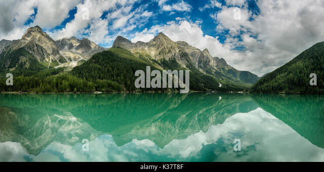 Lake of Anterselva surrounded by mountains with blue sky and clouds in the background on a summer day, Sud Tirol, - Stock Image