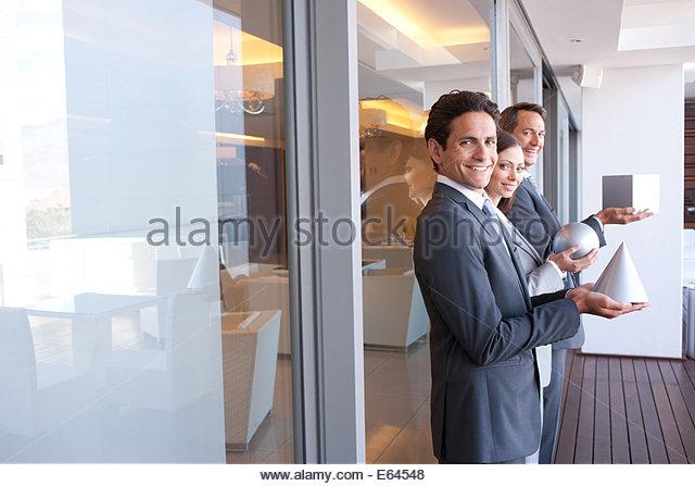 Business people holding geometric shapes - Stock Image