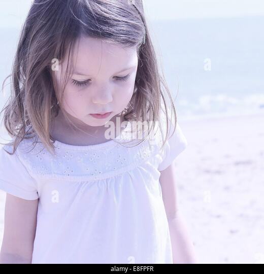Portrait of girl standing on beach - Stock Image
