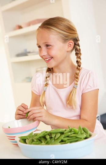 Happy girl splitting peas in kitchen - Stock Image