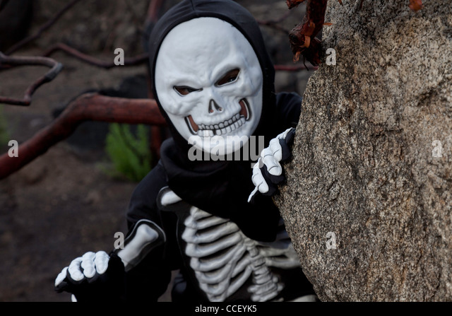 Boy dressed as skeleton creeping out - Stock Image