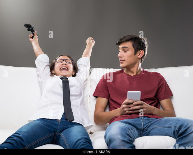 couple of brothers on a sofa as the sister shouts because of her victory on a videogame while her brother on his - Stock Image