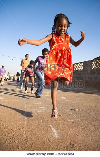 Girls playing hopscotch on street - Stock-Bilder