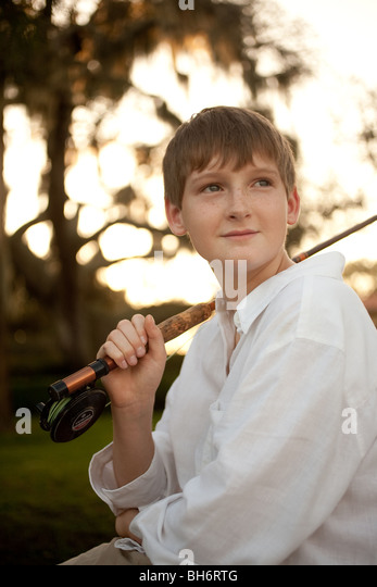 A young boy goes fly fishing. - Stock Image