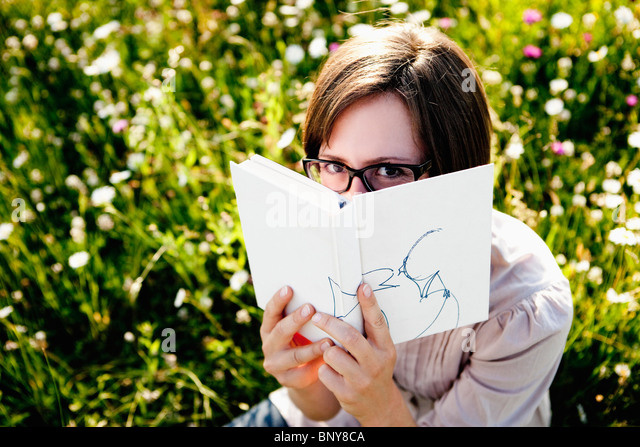 Woman hiding behind book - Stock Image