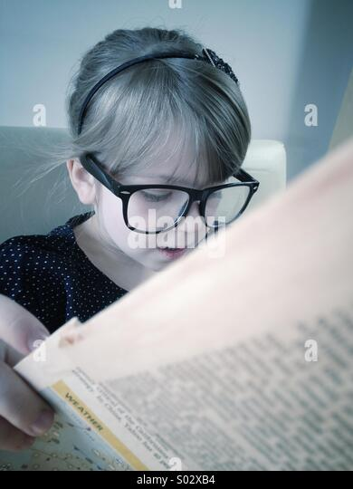 Little girl reading newspaper - Stock Image