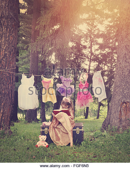 A girl is dressed as a princess reading a book in the woods with costumes hanging from a clothesline for an education - Stock Image