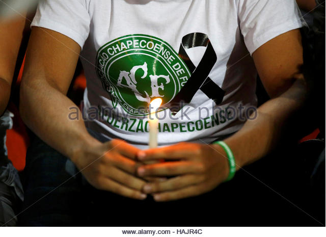 A fan of Atletico Nacional soccer club holds a candle and wears a shirt in support while paying tribute to the players - Stock-Bilder