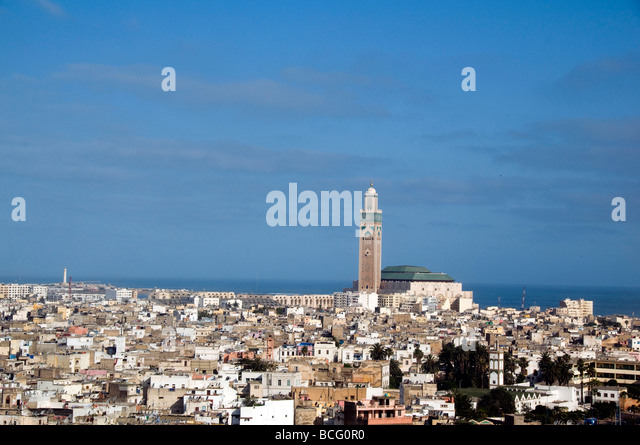 Hassan II Mosque hassan mosque casablanca morocco large rooftop cityscape homes houses condos residences seaside - Stock Image