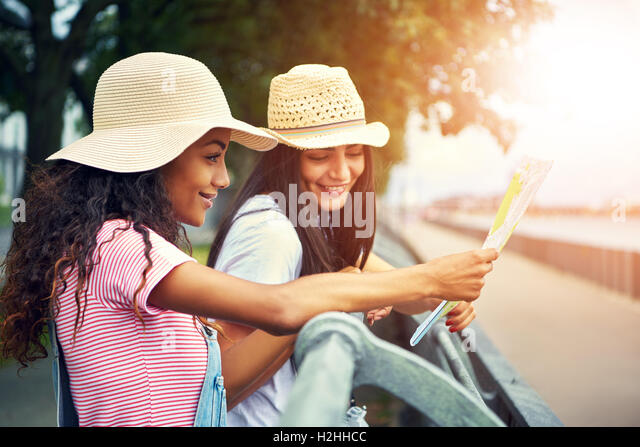 Women outside leaning against jogging path railing wear straw hats and smile while they read a map - Stock Image