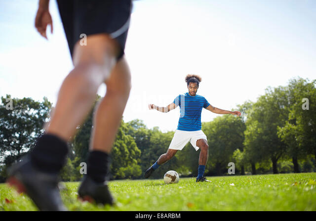 Young couple playing football together in park - Stock Image