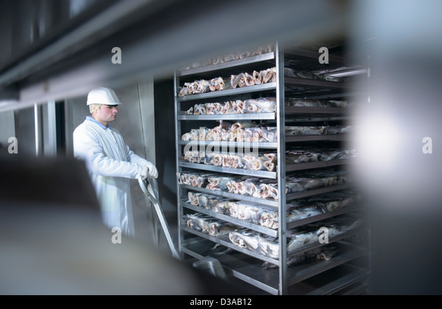 Worker pushing pallet truck through food factory - Stock Image