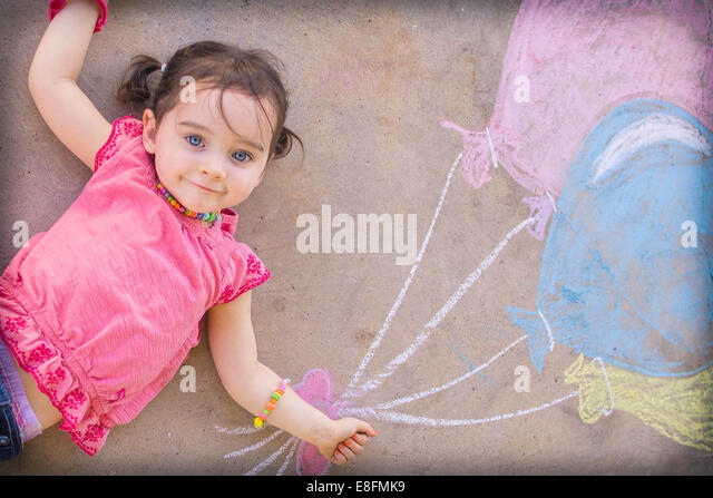 Texas, United States of America Little Girl Laying On Ground With Chalk Drawn Balloons - Stock Image