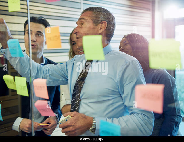 Half body portrait of businessman sticking note on glass, colleagues in background - Stock Image