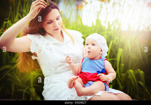 Happy mother playing with child in summer park. Happy healthy family. - Stock Image