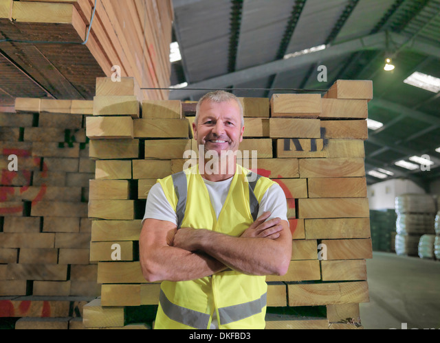Portrait of worker standing in port store, smiling - Stock Image