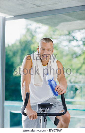 Man on stationary bicycle drinking water - Stock Image