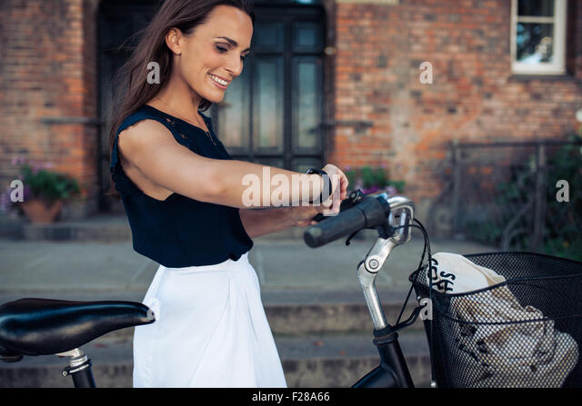 Young woman with a bike checking the time on her wristwatch. Happy woman with bicycle looking at watch, outdoors. - Stock Image