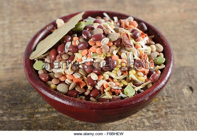 Pearl barley green lentils red lentils aduki beans mung beans soup vegetables bay leaf onions tomato flakes in ceramic - Stock Image