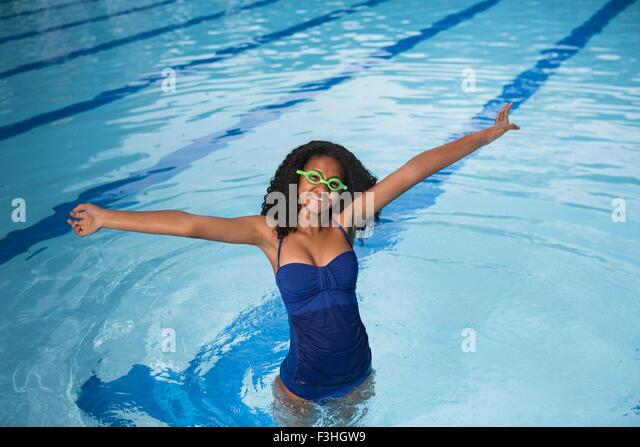 Portrait of girl standing in swimming pool wearing swimming goggles, arms raised, looking at camera smiling - Stock Image