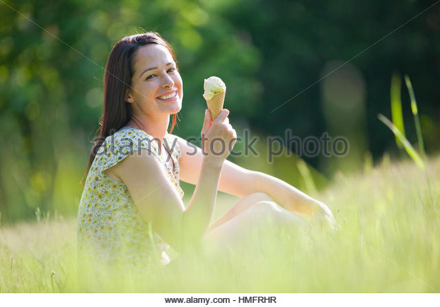 Portrait happy woman eating ice cream cone in sunny summer grass - Stock-Bilder