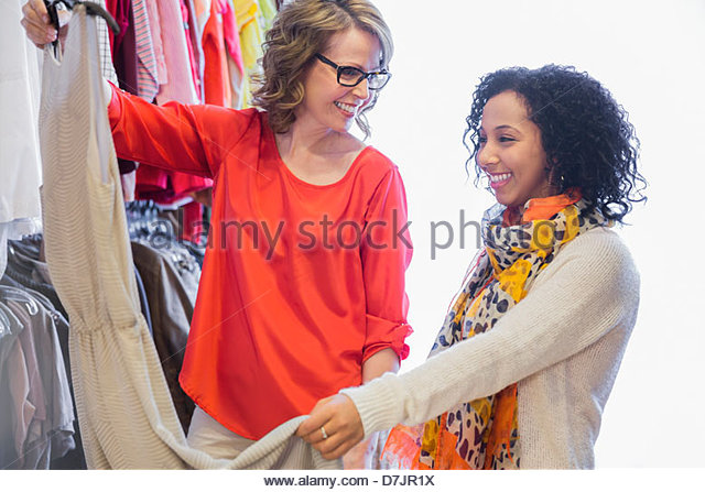 Female small business owner assisting customer with clothing choice - Stock Image