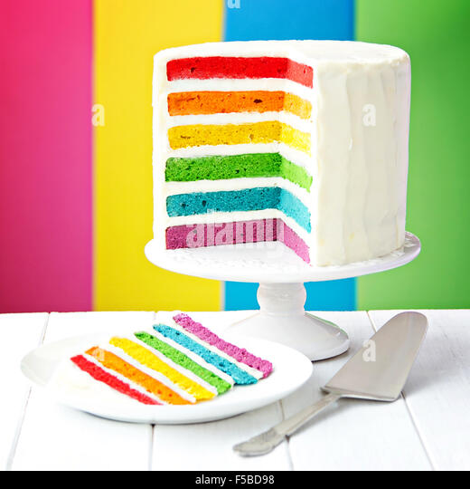 Rainbow layer cake on a cake stand - Stock Image
