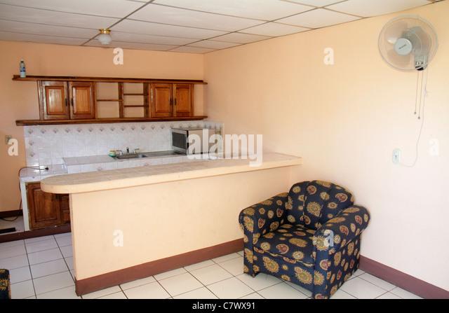 Managua Nicaragua Hotel Villa Angelo suite hotel lodging budget fan chair kitchenette plain decor - Stock Image