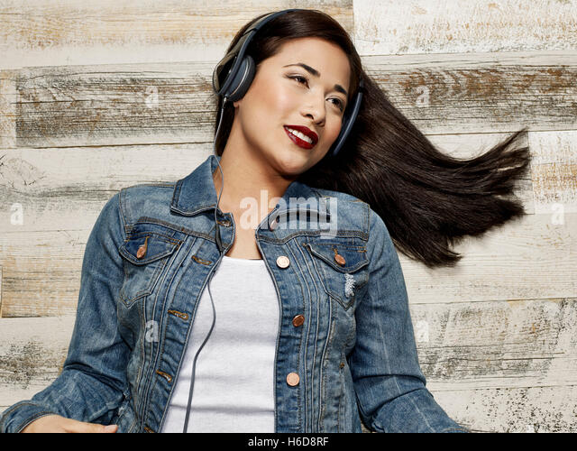young woman on wood floor smiling listen to music in headphones - Stock Image