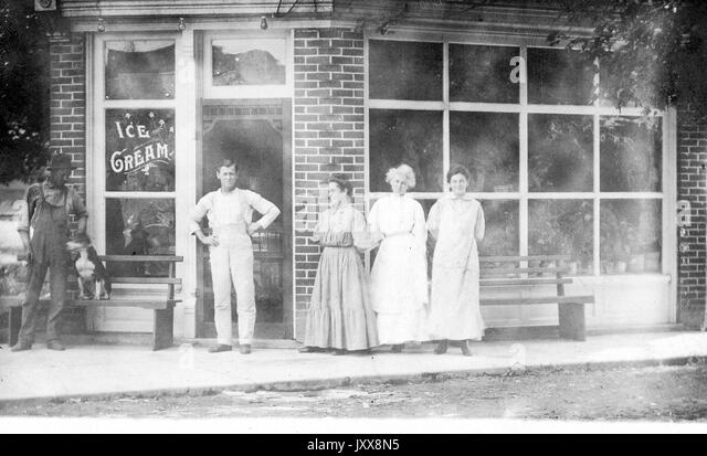 Three Caucasian women and a mature Caucasian man with neutral happy expressions stand in front of a storefront that - Stock Image