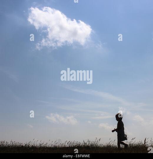 Silhouette of girl walking in rural landscape - Stock Image
