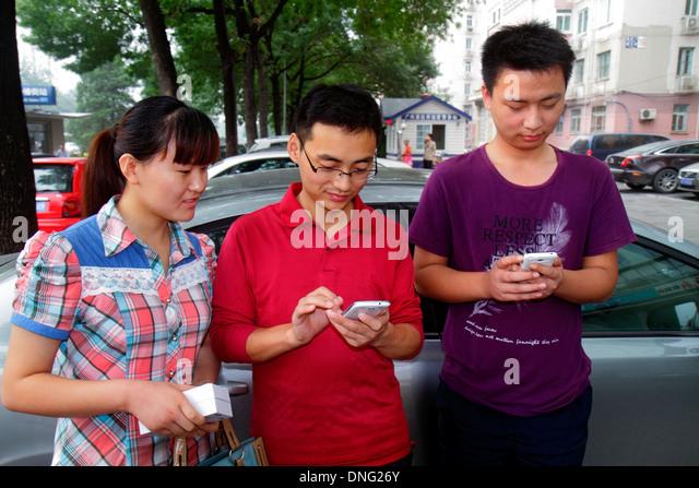 China Beijing Xicheng Asian man woman smartphone texting - Stock Image