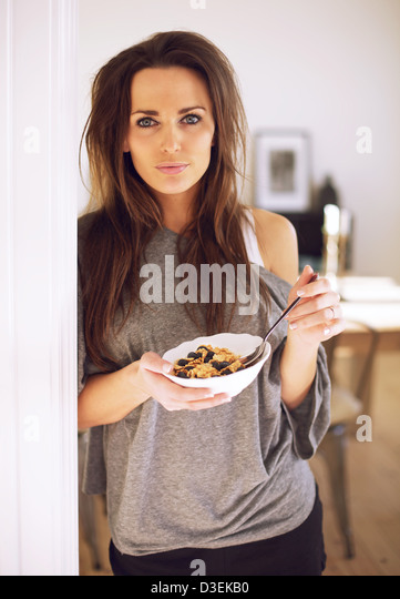 Woman with a spoon and a bowl of cereal looking down - Stock Image