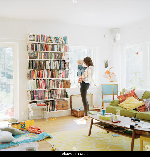 Sweden, Woman with her baby (12-17 months) in domestic room - Stock Image