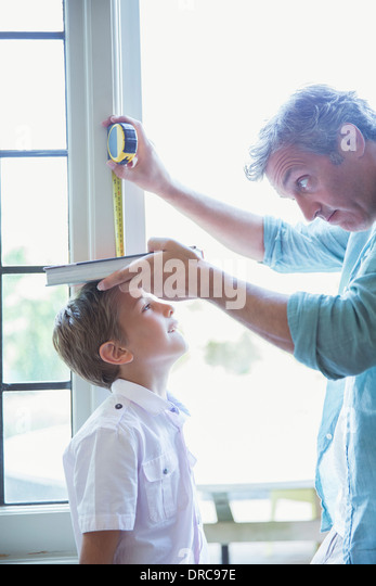 Father measuring son's height on wall - Stock Image