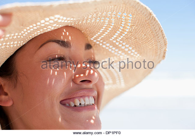 Close up of woman wearing sun hat - Stock Image